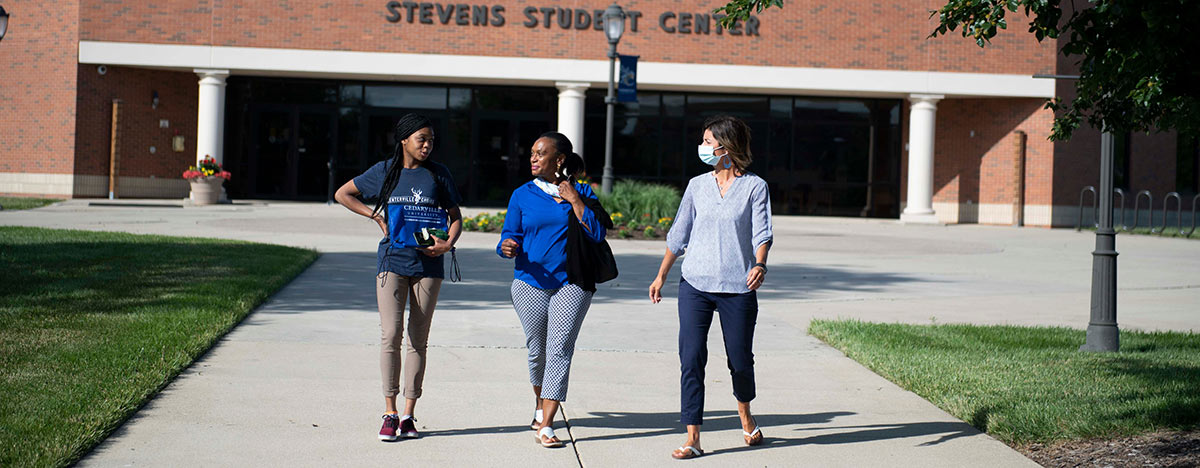 Admissions counselor, parent, and student walking outside the Stevens Student Center.