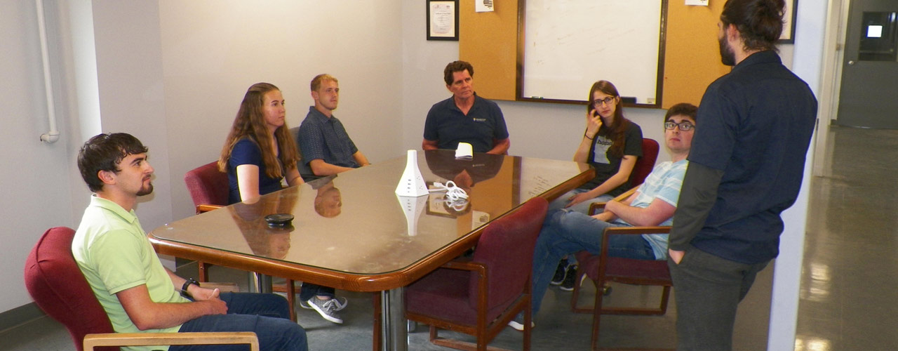 Group of students and professors collaborating around a table