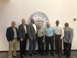 Seven men standing in front of Cedarville Seal
